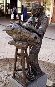 Skulpturen föreställer Professor/ konstnären Asmund Arle verksam i många år i Huddinge, av Jörgen Hammar. Stod tidigare framför scenen i Huddinge C.Förstörde de kommersiella ytorna tyckte det kommunala bostadsbolaget Huge...