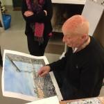 Gugge Norinder på besök hos HKKVs Målargrupp visar en av sina senaste akvareller - Katarinahissen i Stockholm